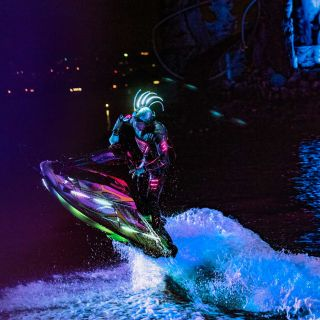 A Man Flying Through The Air While Riding A Wave In The Dark